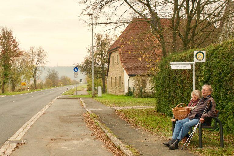 Ehepaar wartet auf einen Mitfahrerbänkla-Fahrer