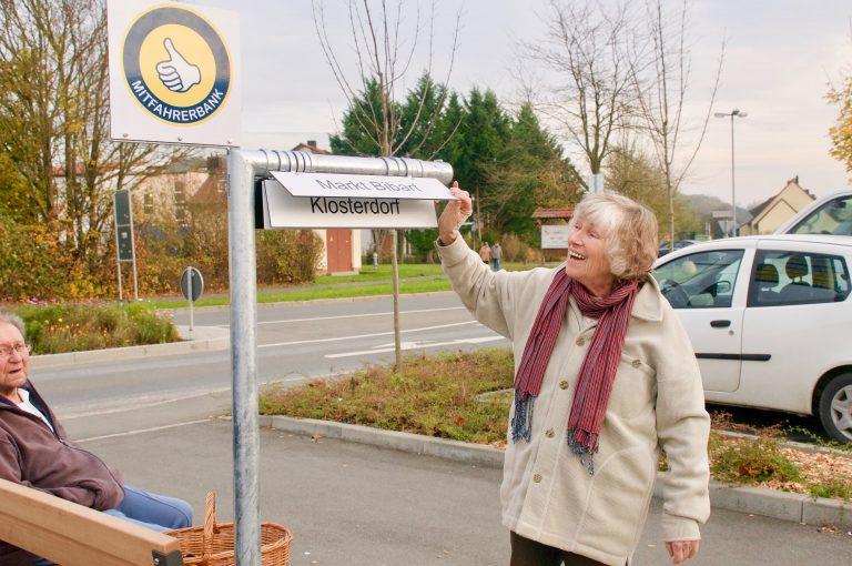 Seniorin stellt ihr Ziel beim Mitfahrerbänkla (Mitfahrerbank) ein